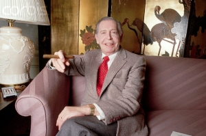 1986 --- Original caption: Portrait of comedian Milton Berle. He is shown seated on a couch, smoking a cigar. Photograph, 1986. --- Image by © Lynn Goldsmith/Corbis
